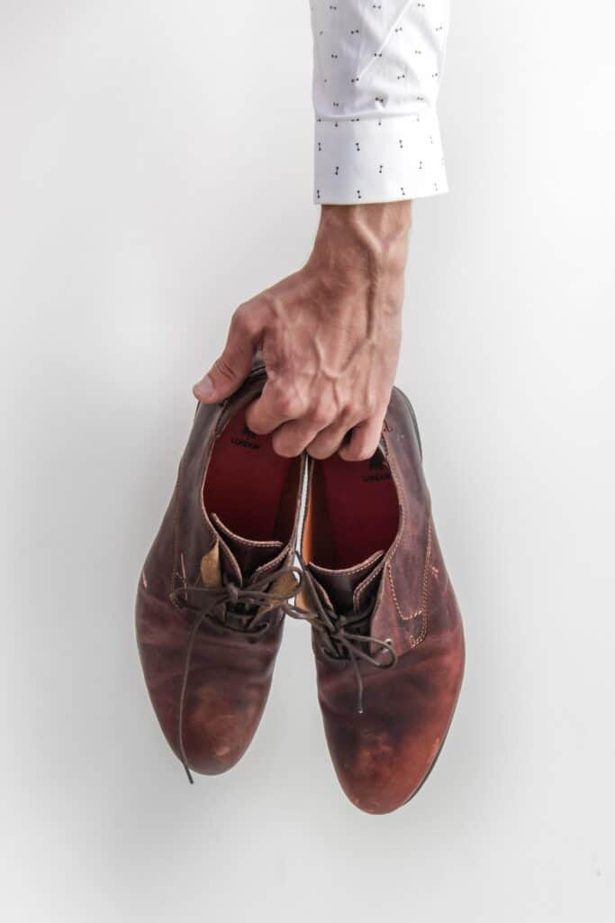 A man holding brown dress shoes