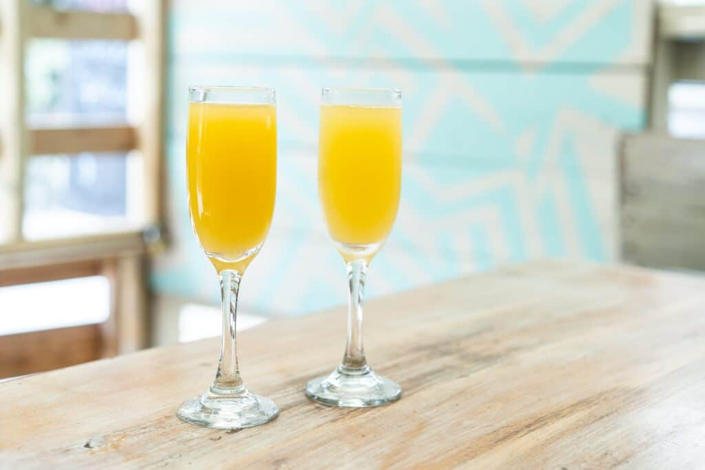 two glasses with orange juice on wood table
