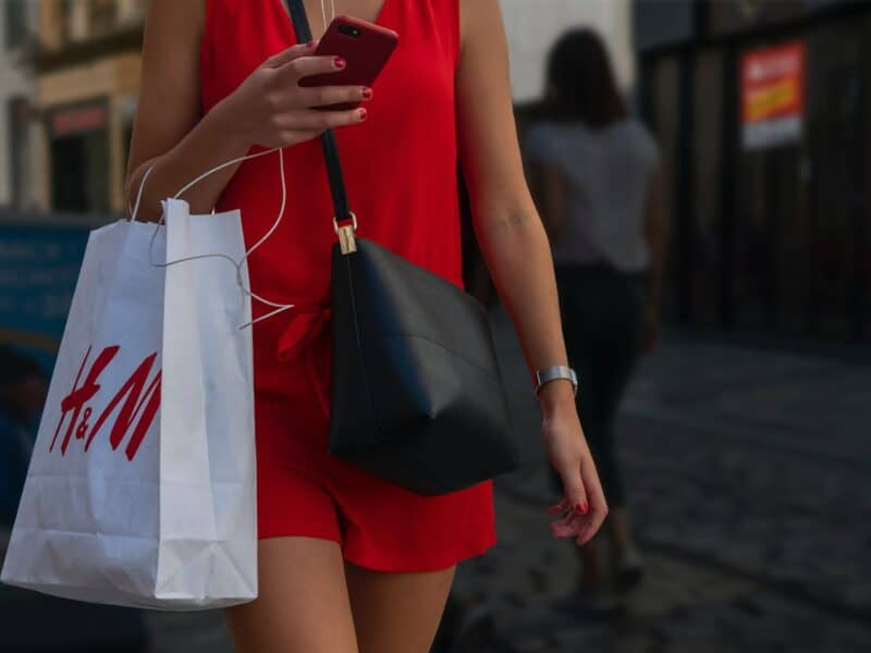 girl in red dress holding H&M bag