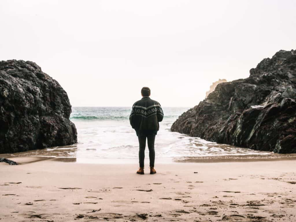 man in dark jacket standing on beach looking at ocean