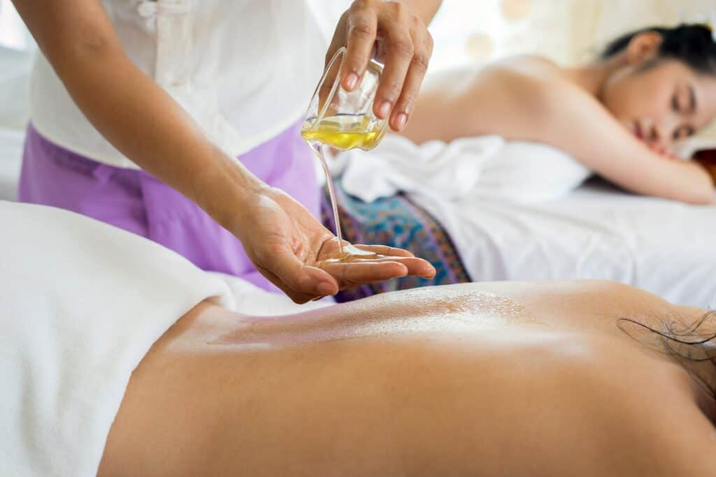 person putting massage oil on another person