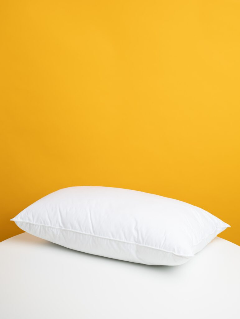 yellow background with white sheets and one white pillow