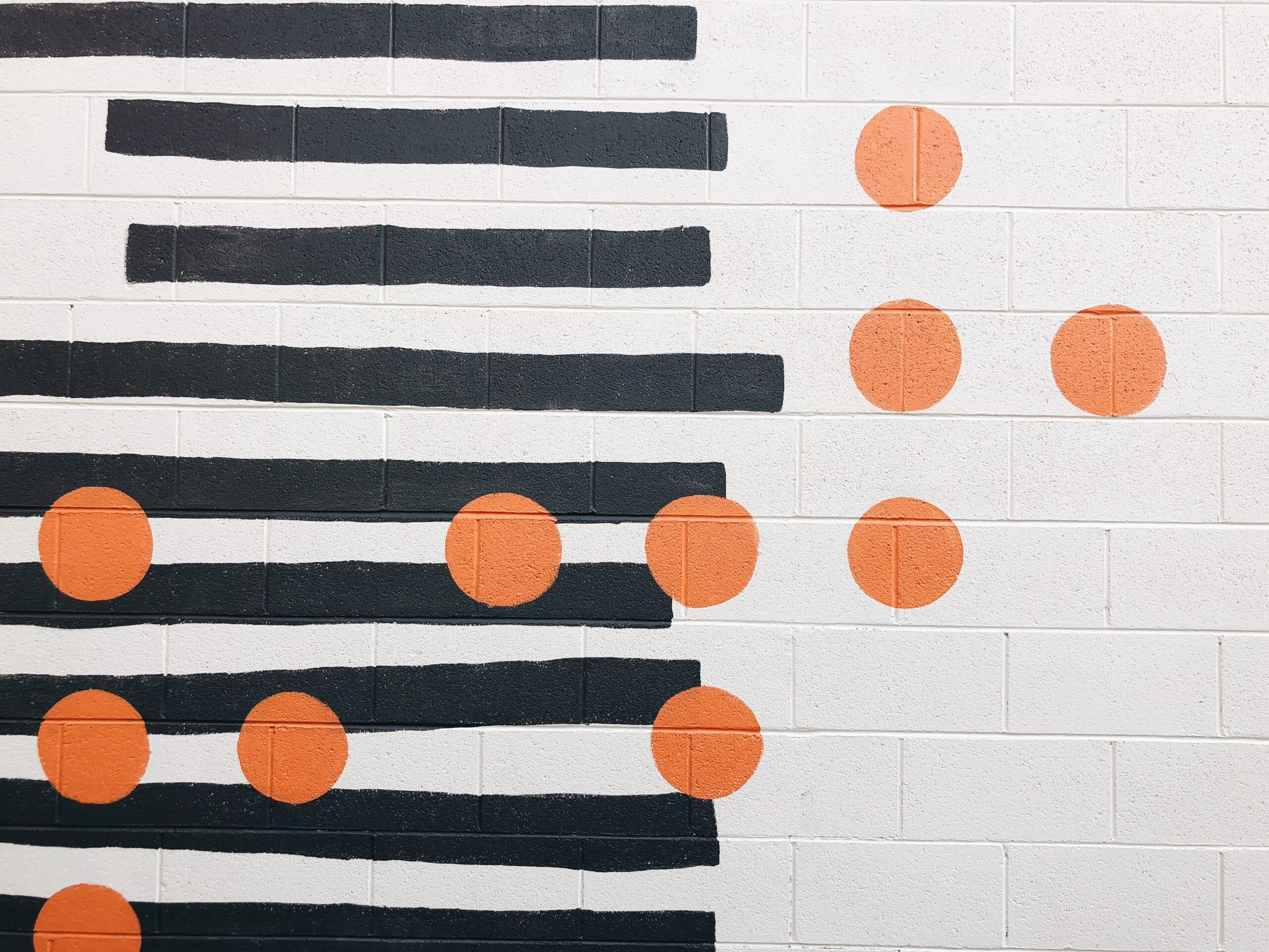 white brick wall painted with black stripes and orange dots