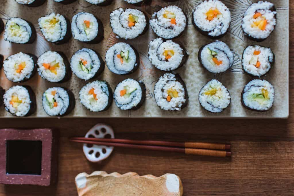 plate of sushi rolls with chopsticks to the side