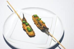 two small deep fried chicken on stick