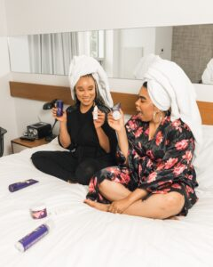 two girls sitting on bed holding skin care products