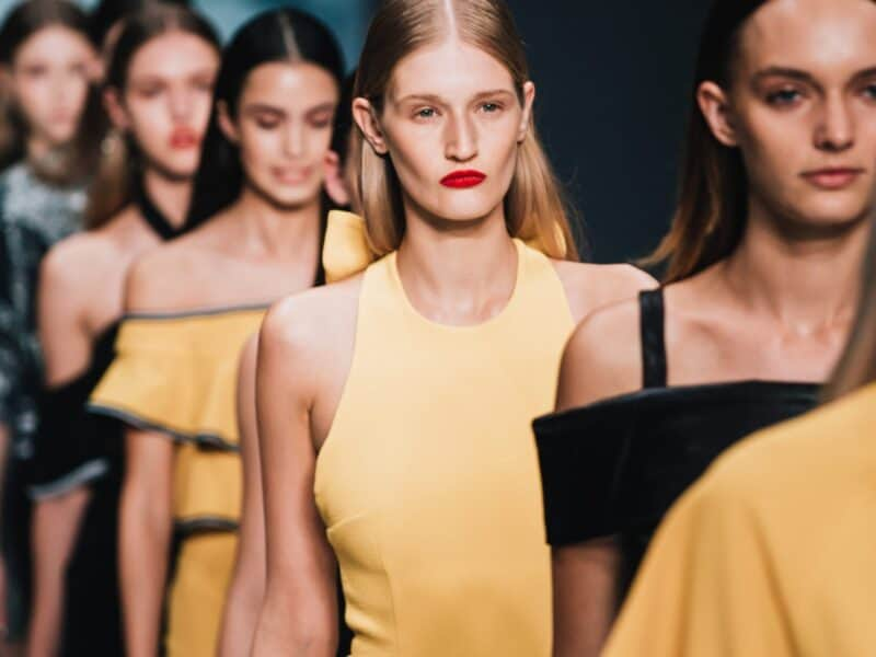 models wearing yellow and black walking runway