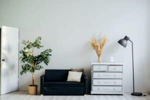 blue couch and white dresser against white wall