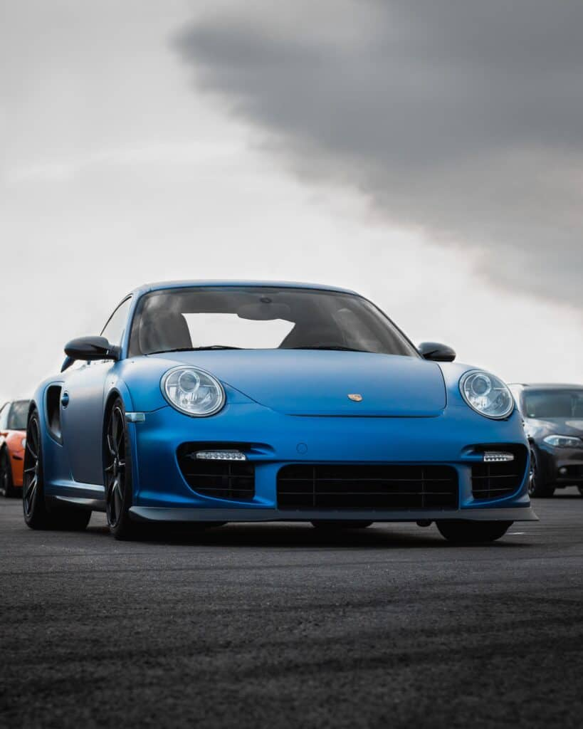 blue Porsche on road