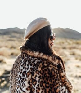 girl wearing leopard print coat and white hat