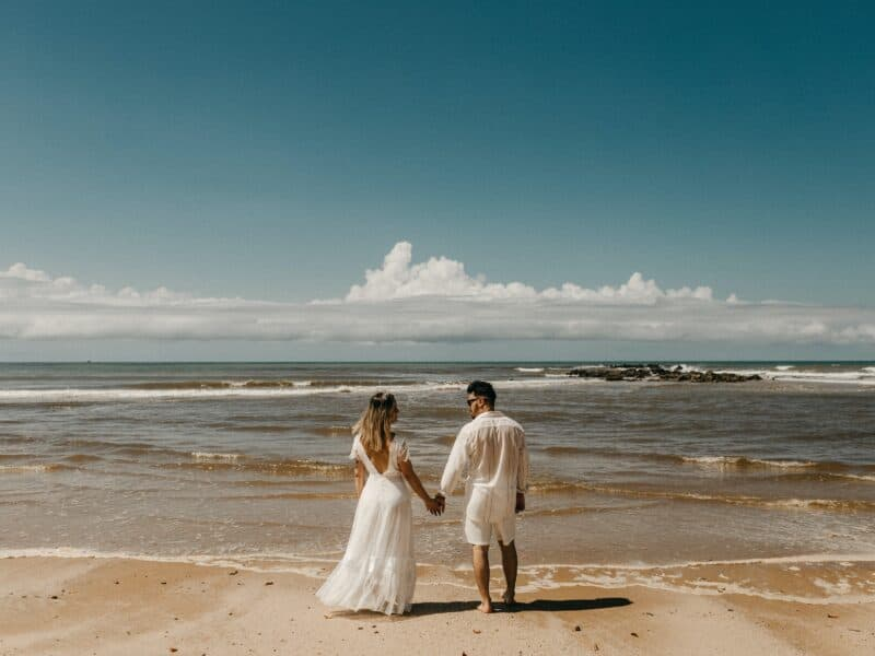 couple dressed in white standing on beach looking at ocean