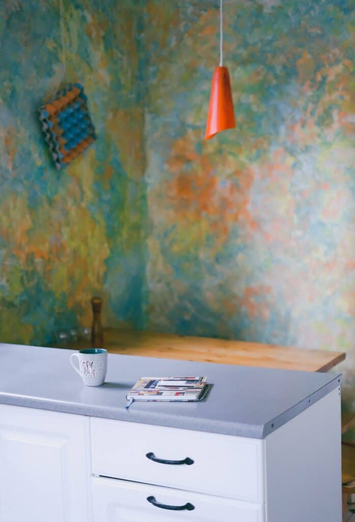 white kitchen counter with colorful wallpaper in background