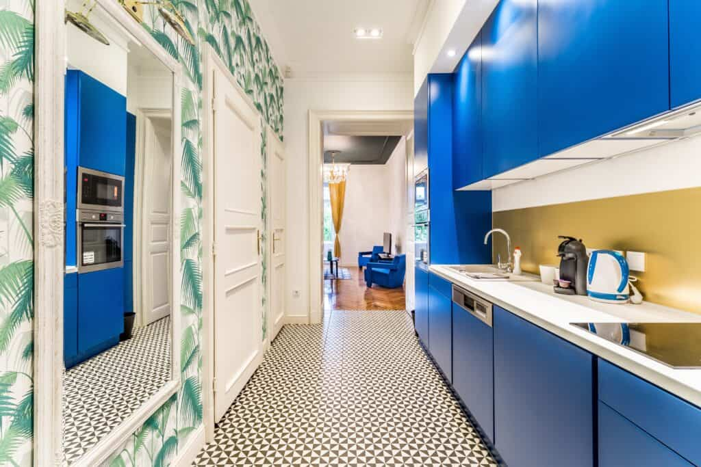 kitchen with blue cabinets and palm leaf wallpaper