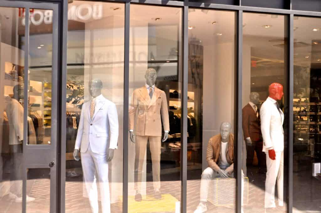 mannequins dressed in suits in storefront window