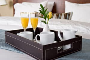 tray of orange juice and coffee on hotel bed