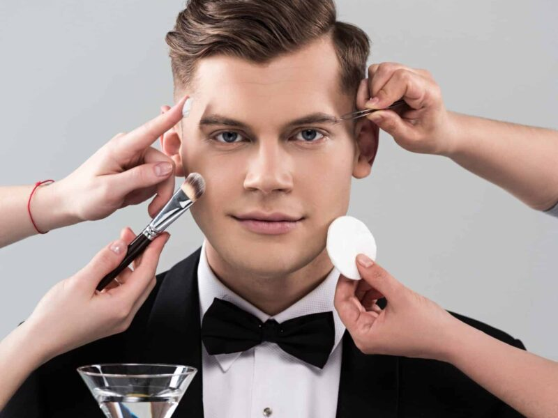 Man in suit holding cocktail, getting makeup put on