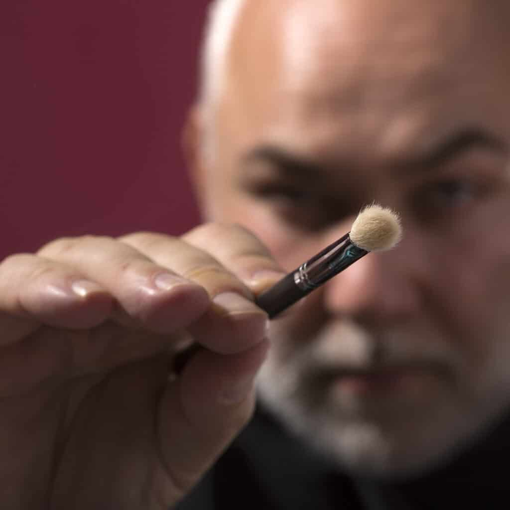 Man holding makeup brush, with brush in focus and man blurred in the background
