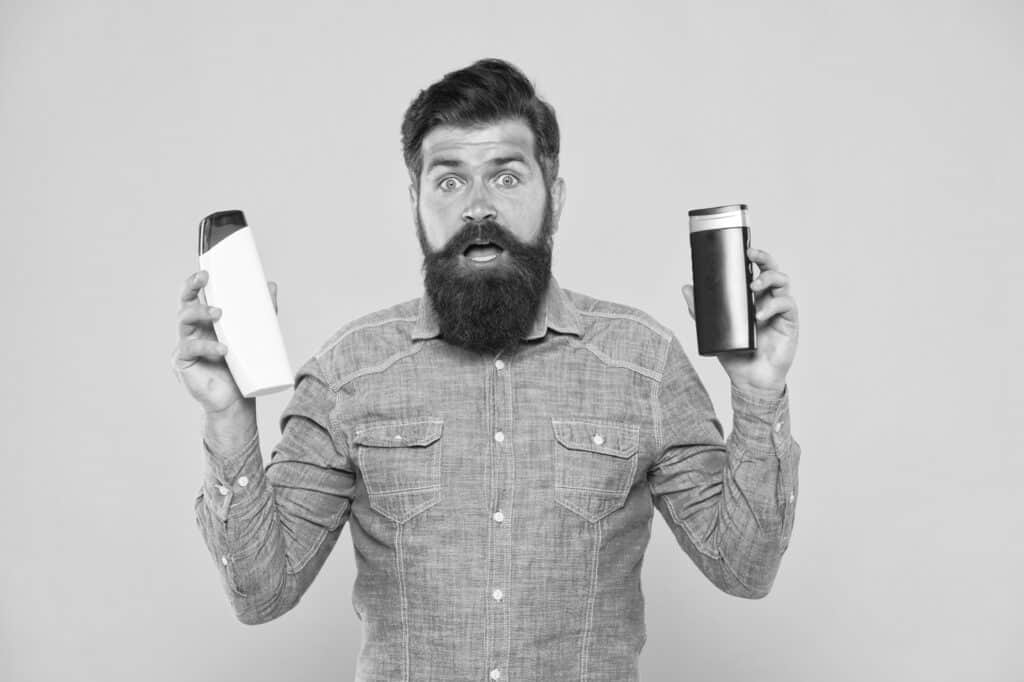black and white photo of a man holding two bottles with a shocked look on his face