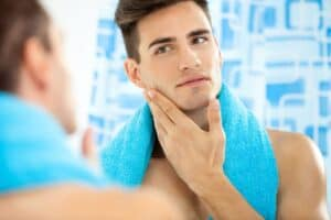 man with blue towel around his neck looking in mirror and touching his face