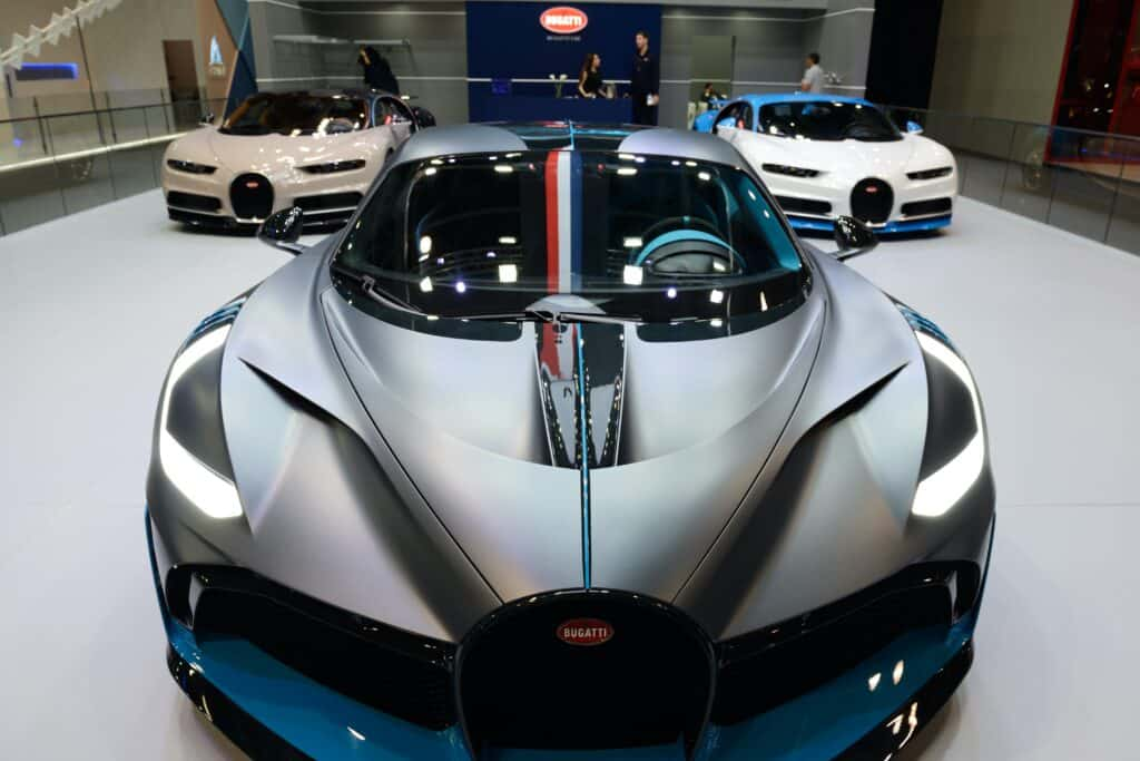 front of grey bugatti on showroom floor