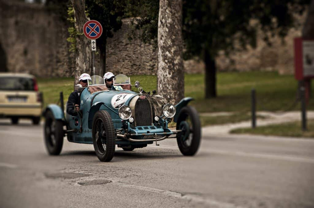 Two men driving one of the original Bugatti models