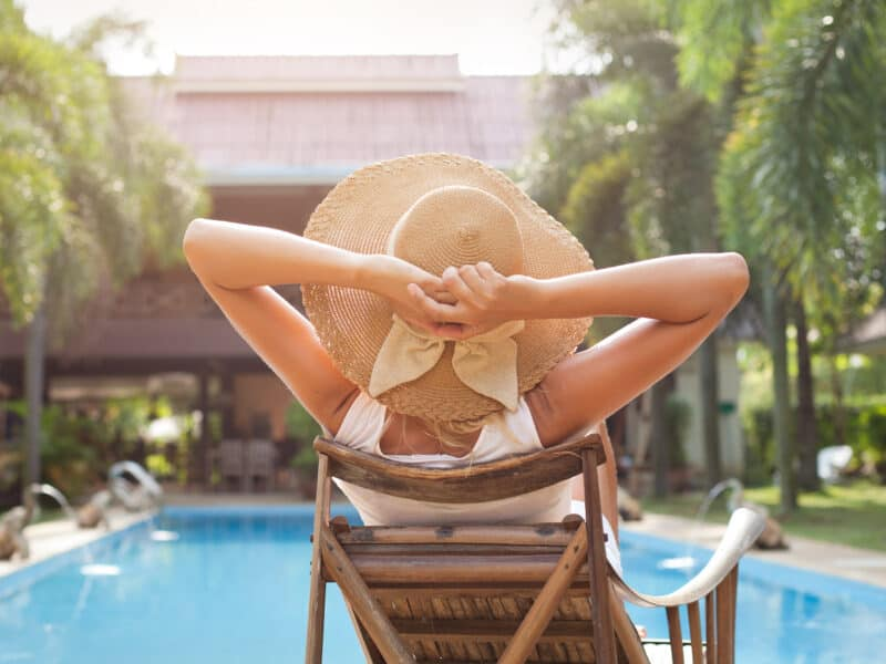 girl in sun hat sitting in pool chair