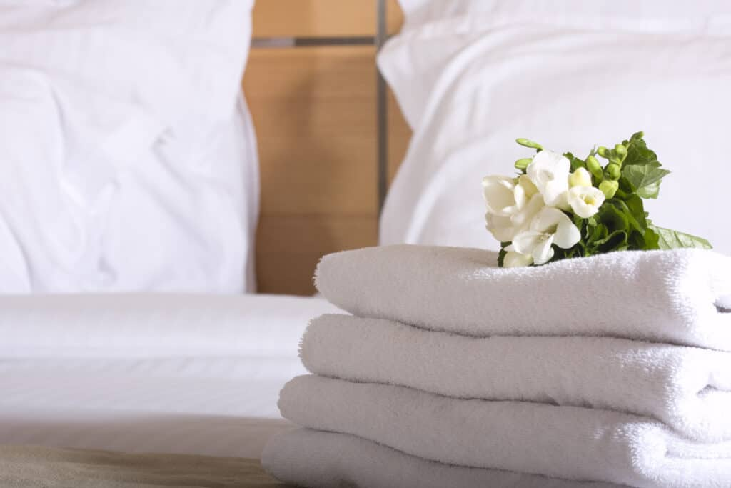 stack of white towels on bed