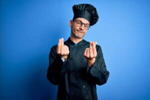 young chef wearing black chef uniform, holding up fingers