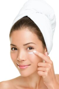 Skin care woman putting on face cream