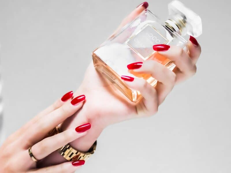 womens hands holding coco chanel perfume bottle