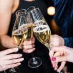 people holding flutes of champagne clinking glasses