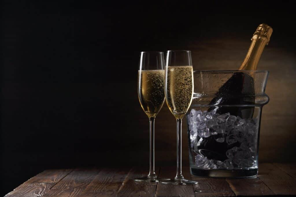 two champagne glasses and bottle in bucket of ice