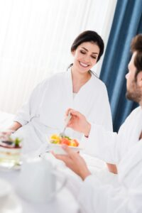 Couple in white robes enjoying breakfast in bed