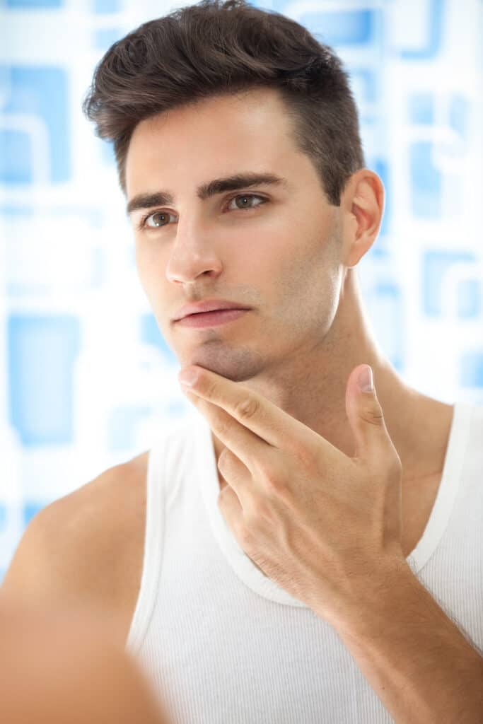 man touching face looking in mirror