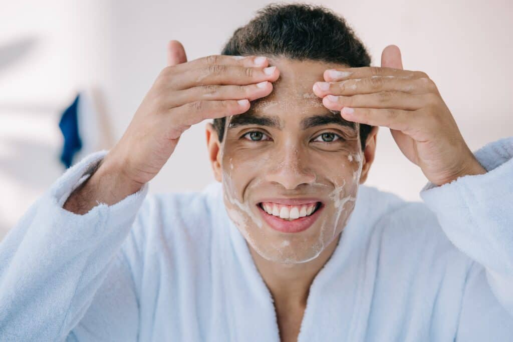 man washing face with face wash