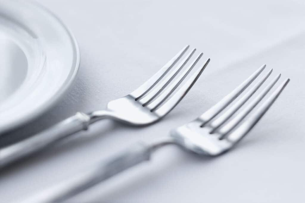 two forks sitting on table next to plate