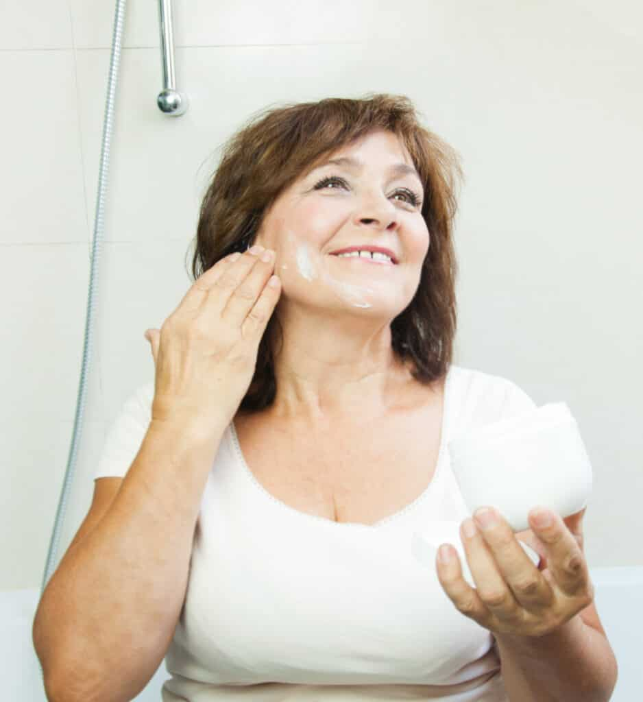 women over 50 looking in mirror putting on moisturizer