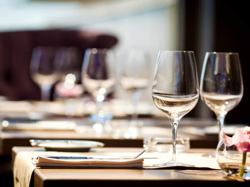 table in restaurant set with plates, linens, and wine glasses