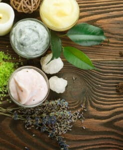 containers full of different natural face cream ingredients on wooden table