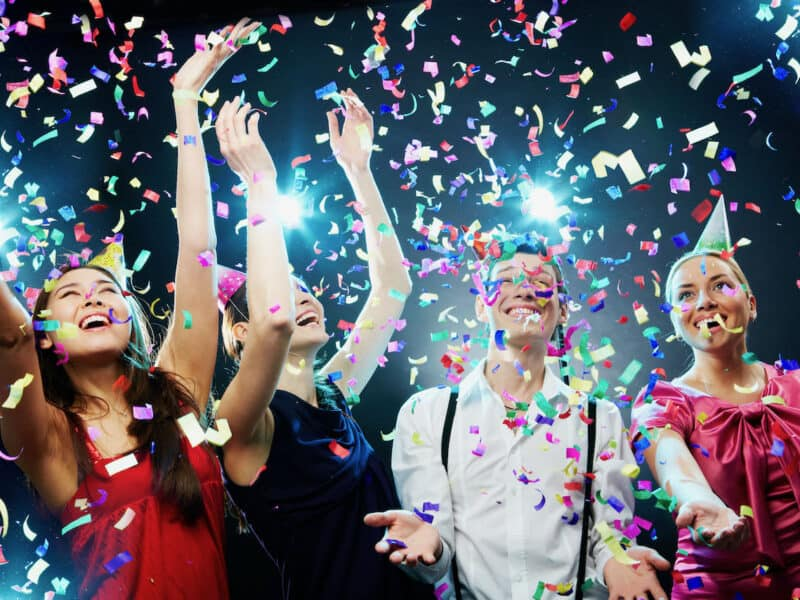 Group of people partying under confetti