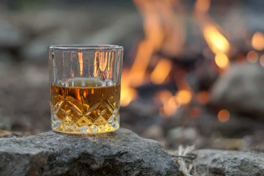 glass of whisky sitting on rock with campfire in the background