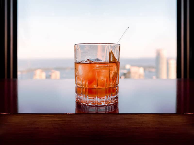 glass of whisky sitting on table overlooking city skyline