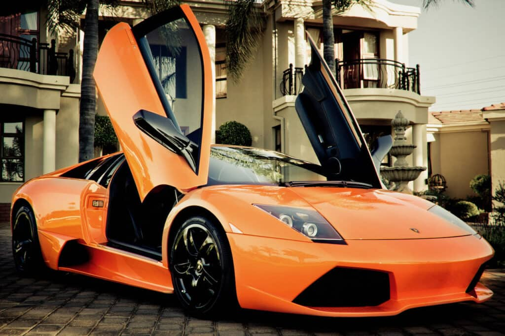 Orange lamborghini with doors up parked on side of the road.