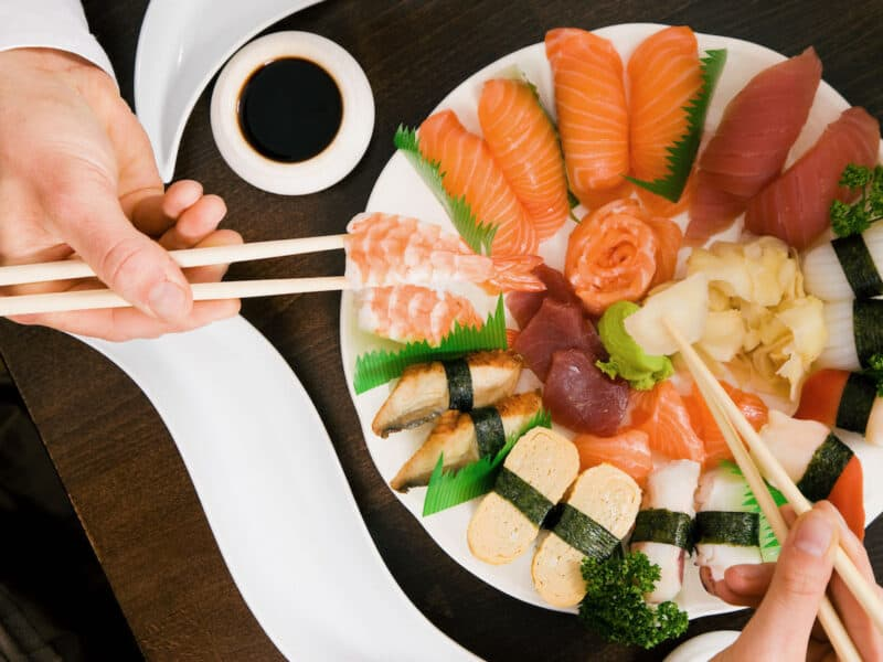 top view of hands holding chopsticks and picking up sushi rolls off of white plate