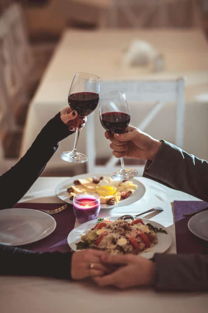 a couple clinking wine glasses over dinner