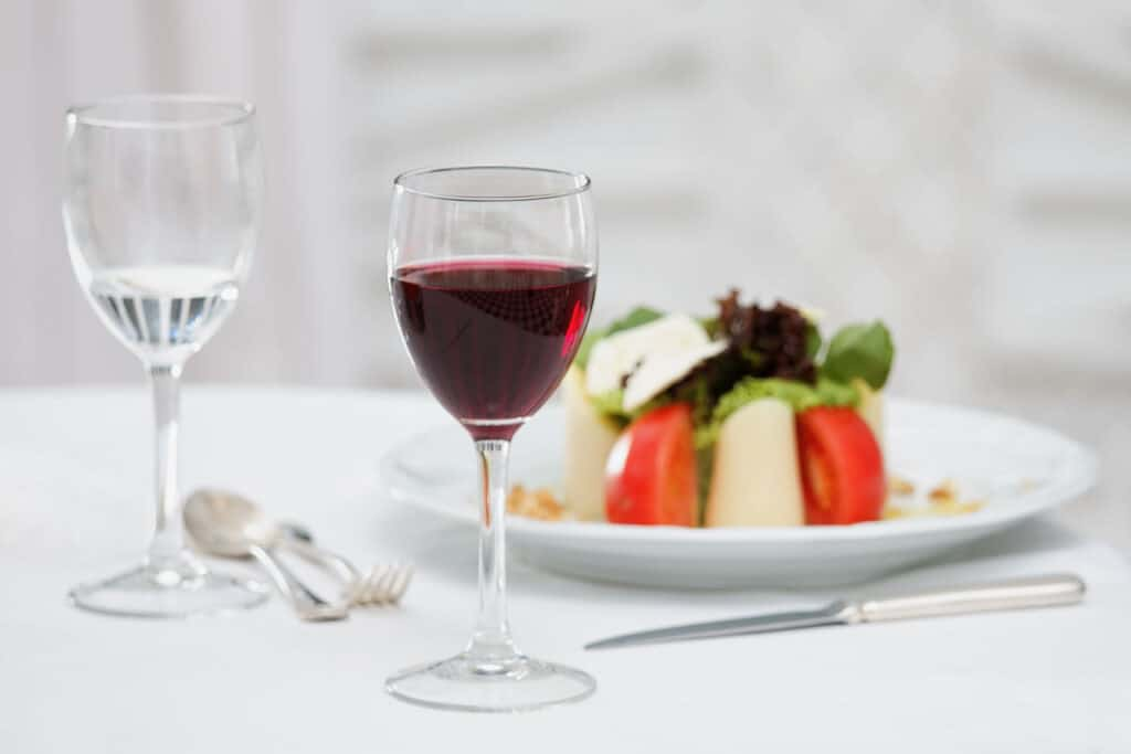 two glasses of wine sitting on white table cloth