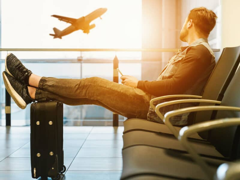 man sitting in airport watching plane take off