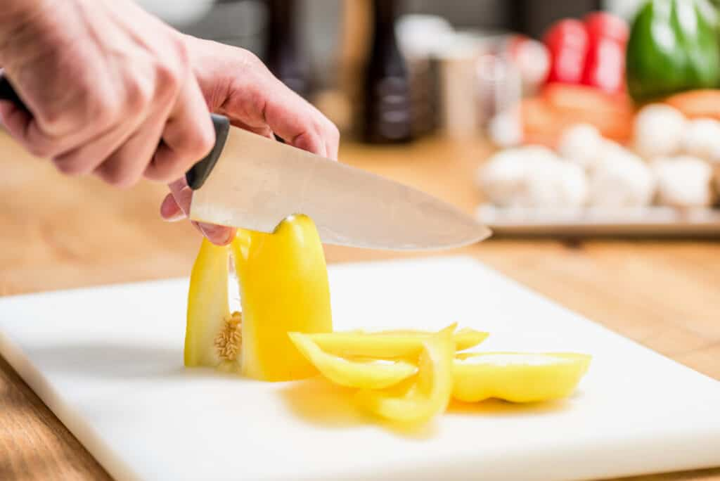 close up of chef hands cutting a yellow bell pepper