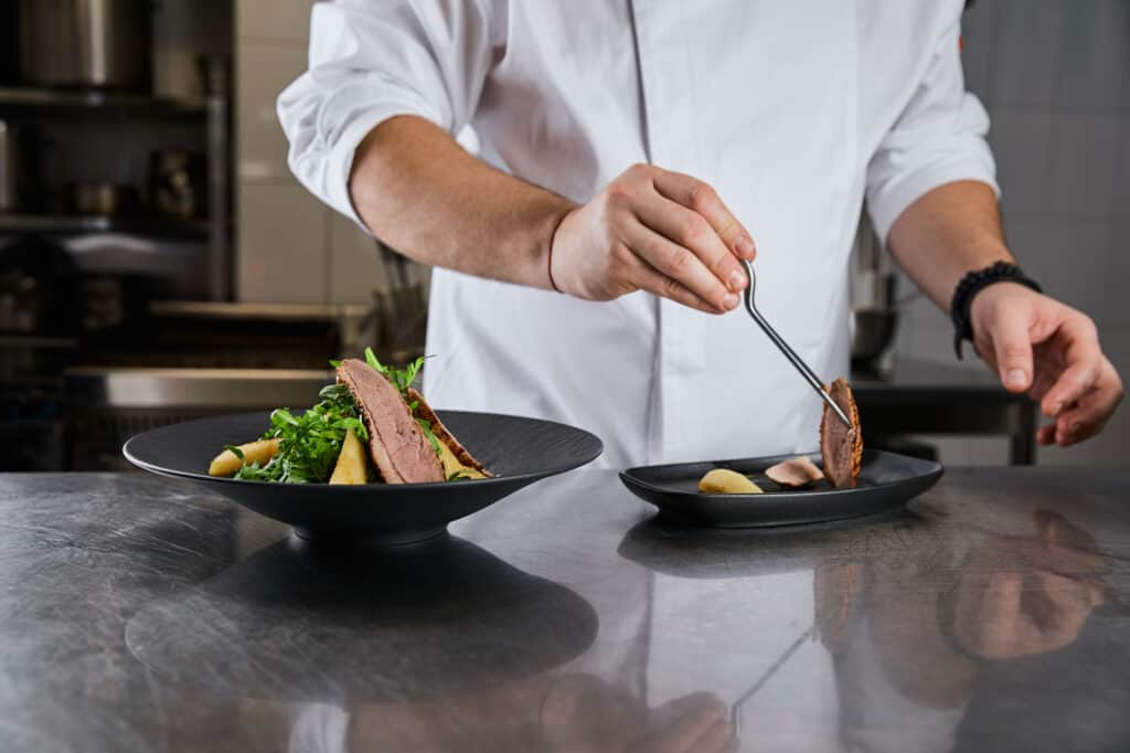 Close up of chef putting finishing touches on a dish