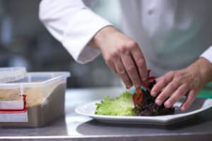 chef preparing a meal, close up of hands putting together a plate